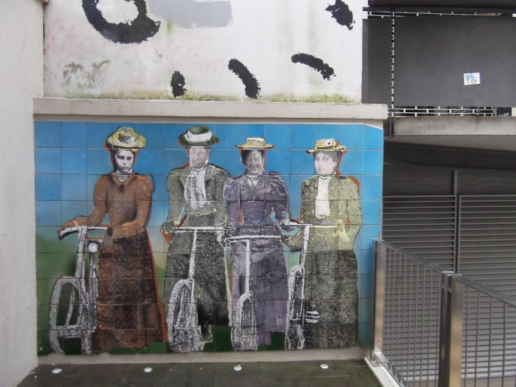 Four frocked up cyclists tiled wall art