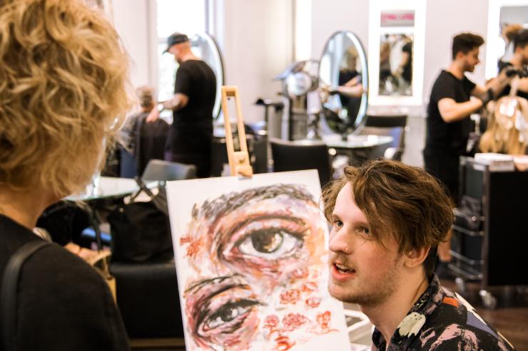 Artist Brendan Hartnett at Rakis on Collins painting event with client
